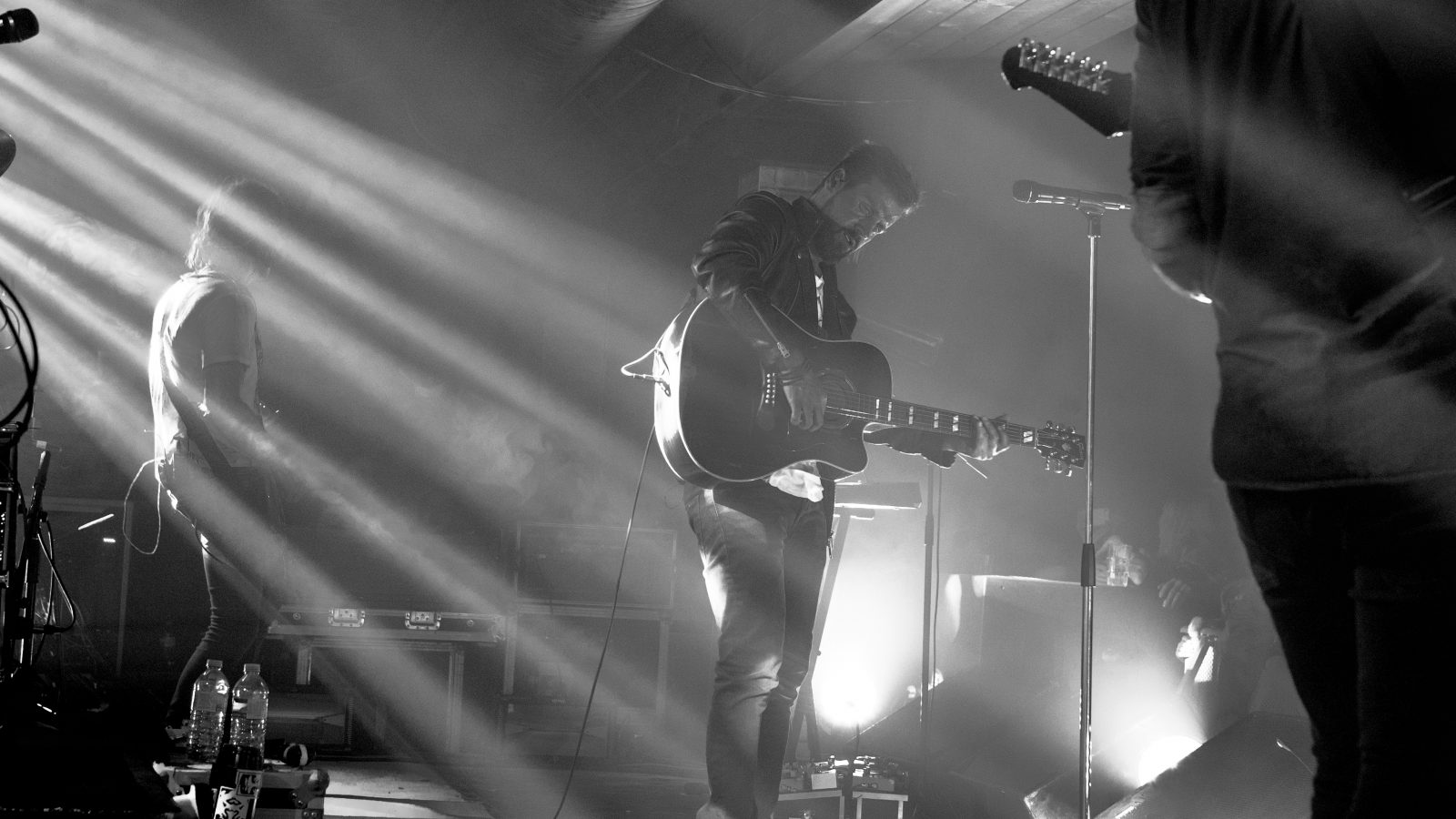 grayscale photography of band member performing on stage